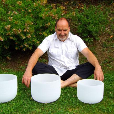 alain-métraux-assis-avec-des-bols-de-cristal
